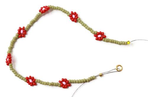 DIY daisy chain armbånd med røde blomster