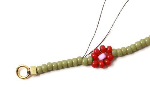 daisy chain armbånd i grønt med røde blomster