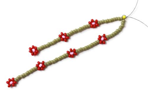 diy daisy chain øreringe med små røde blomster i seedbeads
