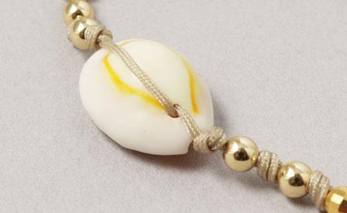 armbånd med cowrie skaller og forgyldte perler